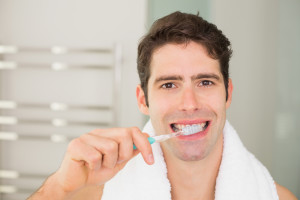 Man Undergoing Invisalign Treatment Brushing Teeth to Prevent Cavities