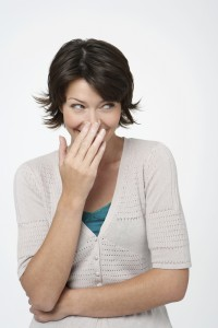 shorthaired woman with hand over mouth